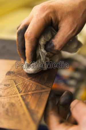 germany bavaria mature man cleaning copperplate