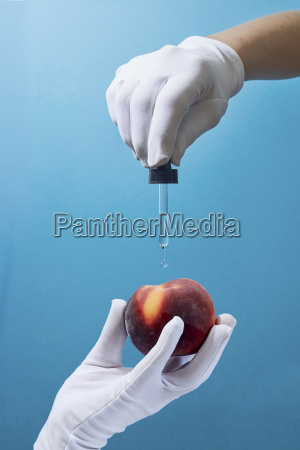 hand with protective glove pipetting on