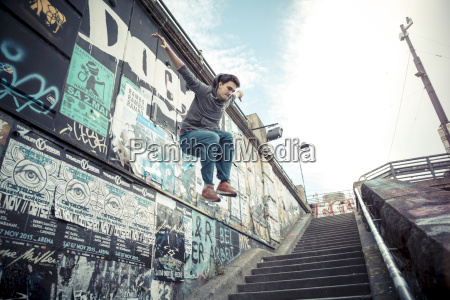 young man jumping off wall