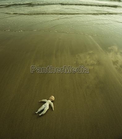 doll lying on wet sandy beach