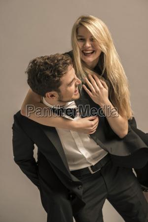 man wearing tuxedo giving laughing blond
