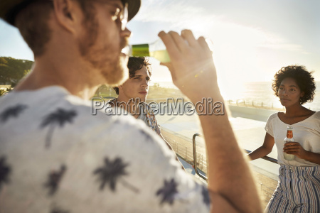 friends drinking beer on highboard of
