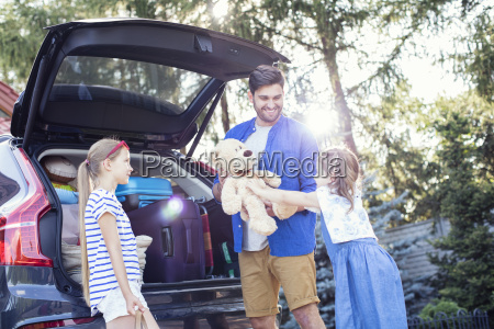 father and daughters packing car boot