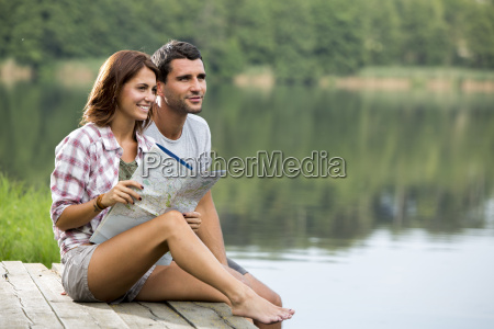 relaxed young couple with map sitting