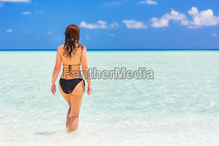 attractive young woman enjoys maldivian beach