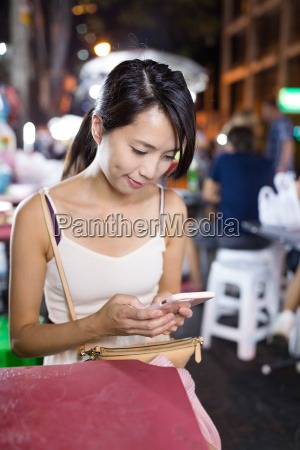 woman using cellphone in night market