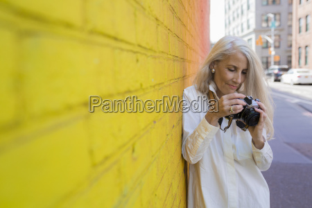 mature woman with camera leaning against