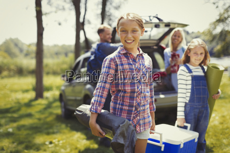 portrait smiling family unloading camping equipment