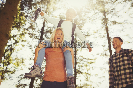 mother carrying daughter on shoulders hiking