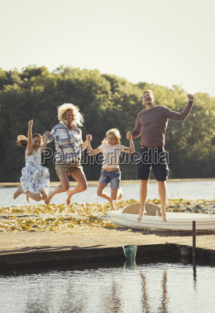 portrait playful family jumping on sunny