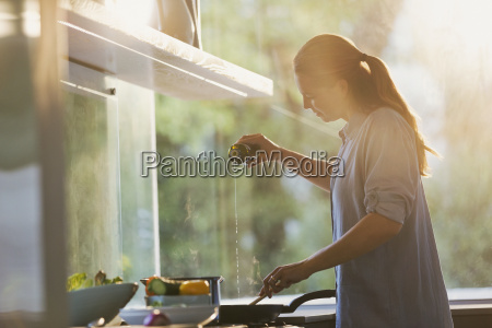 woman pouring oil into pan on