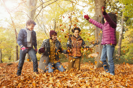playful young family throwing leaves in