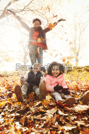 playful mother and daughters throwing autumn