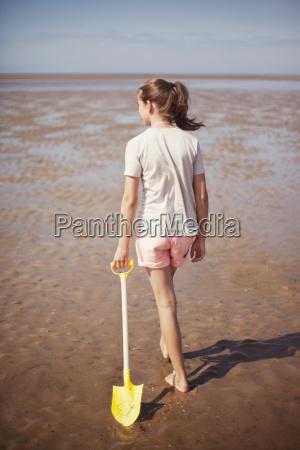 teenage girl dragging shovel in wet