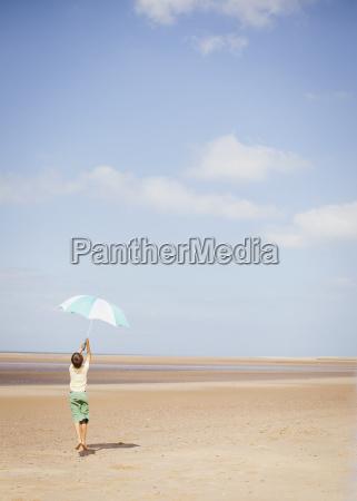 boy holding striped umbrella overhead on