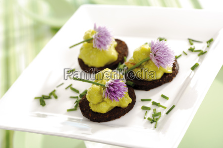 pumpernickel appetizer with avocado cream garnished