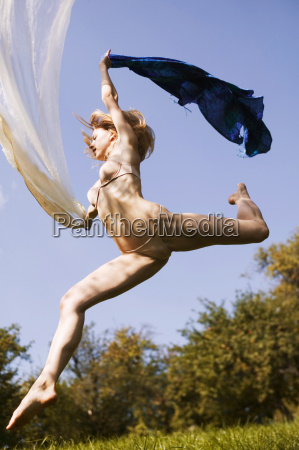 young nude woman in mid air