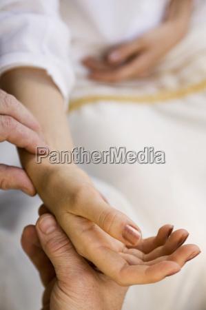 hand feeling womans pulse