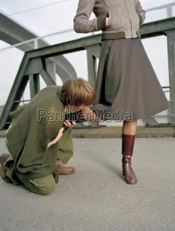 kneeling man kissing foot of woman