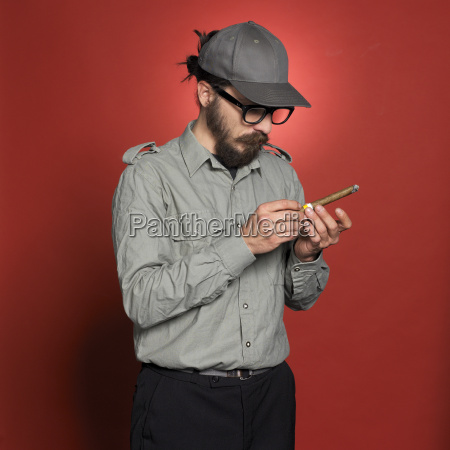 mature man holding cigar against red