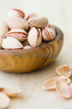 pistachio nuts in wooden bowl close