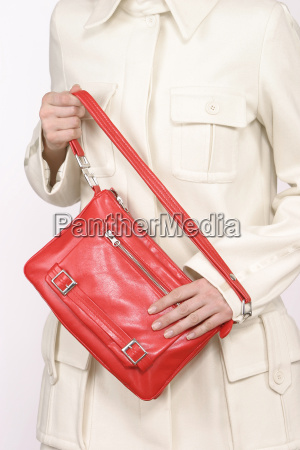 frau die rote handtasche anhaelt