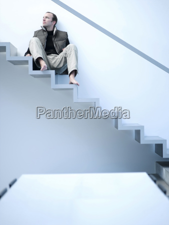 young man sitting on stairs low