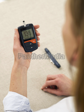 mature woman checking diabetes with glaucometer