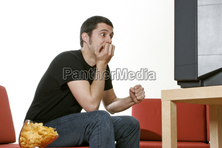 man relaxing on sofa watching football