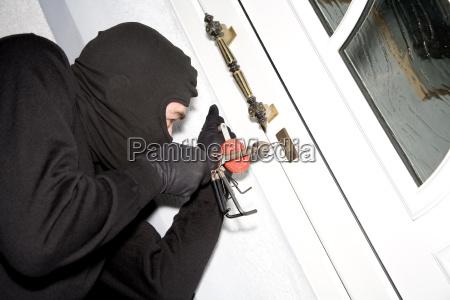 burglar breaking lock close up