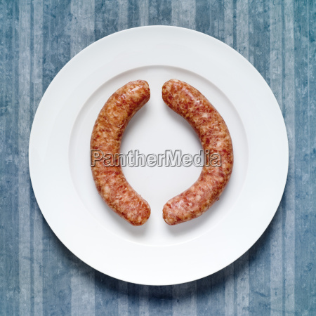 raw sausages on plate elevated view