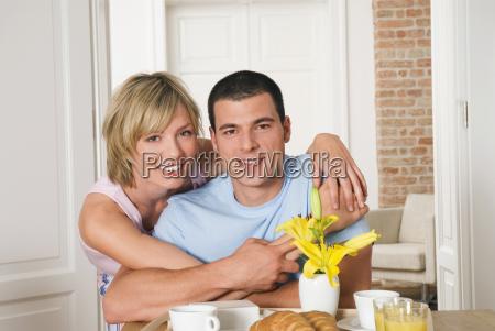 potomstwo pary przytulenie przy sniadaniowym stolem