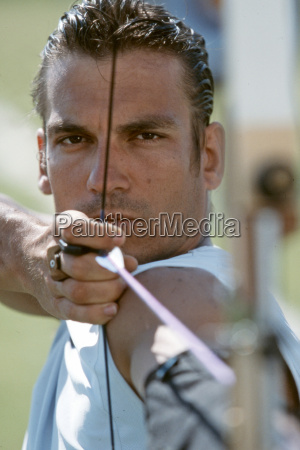 young man aiming with bow and