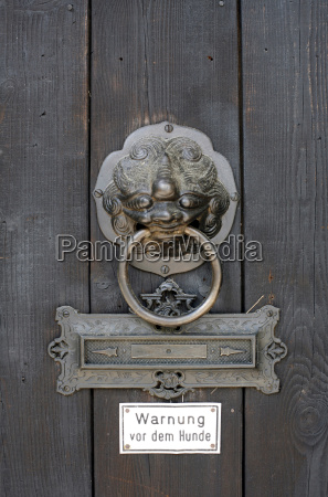wooden door with knocker and warning