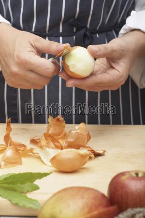 person peeling an onion close up