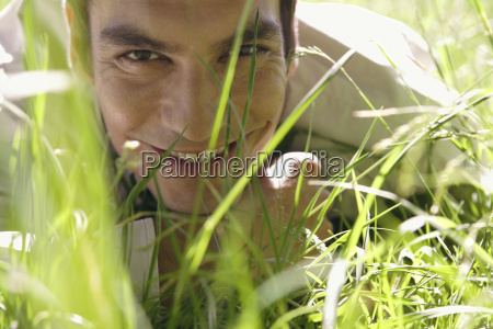 man lying in meadow close up