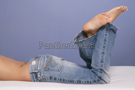 woman on bed wearing jeans