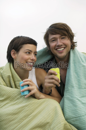 young couple wrapped in blanket smiling