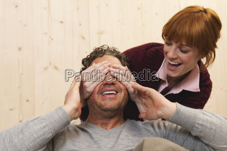 couple fooling about woman covering mans