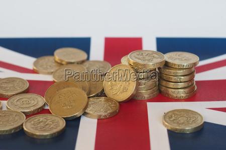 pound coins united kingdom over flag