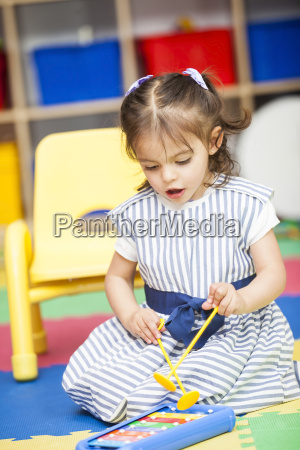 little girl singing and playing a