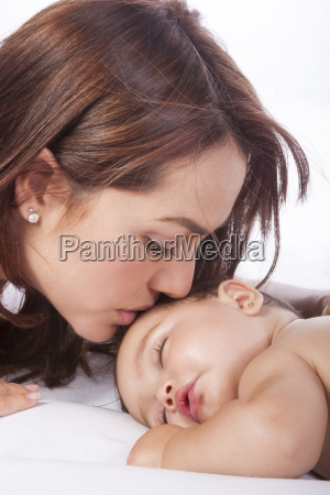 mother kissing her baby girl