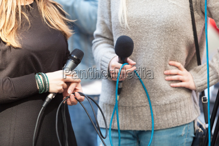 female reporters holding microphones waiting for