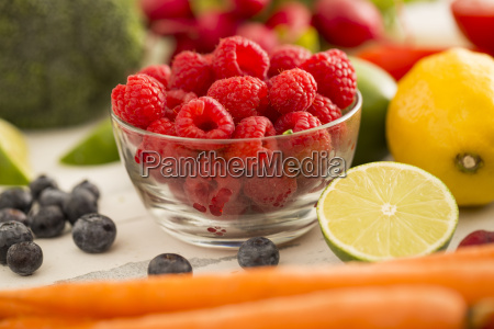 raspberries in bowl surrounded by fruits