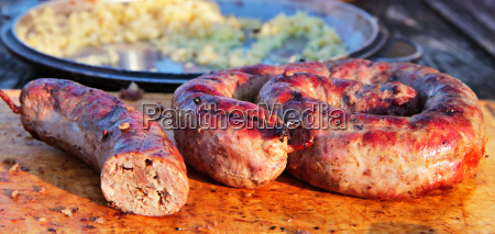 delicious sausages on wooden plate cooked