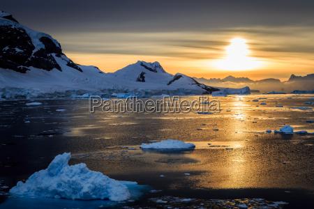 blue icebergs mountains and polar sun