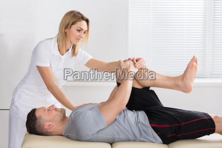 physiotherapist giving knee exercise to a