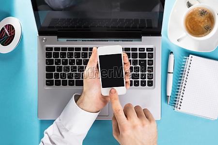 businessman using mobile phone on laptop