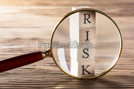 person placing magnifying glass over risk