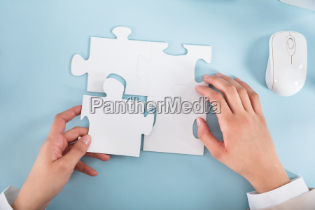 businesswoman joining the jigsaw puzzle pieces